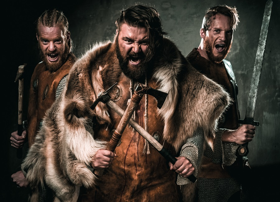 Three men dressed in traditional Viking clothing look at the camera with their mouths open.
