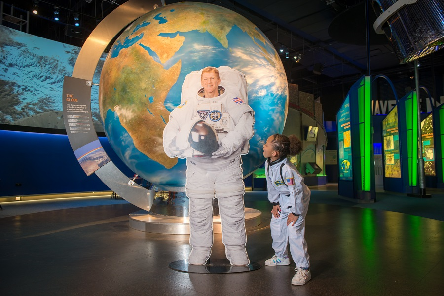 Little girl in a space suit smiling up at a paper cut out of an astronaut at Leicester's Space Centre.