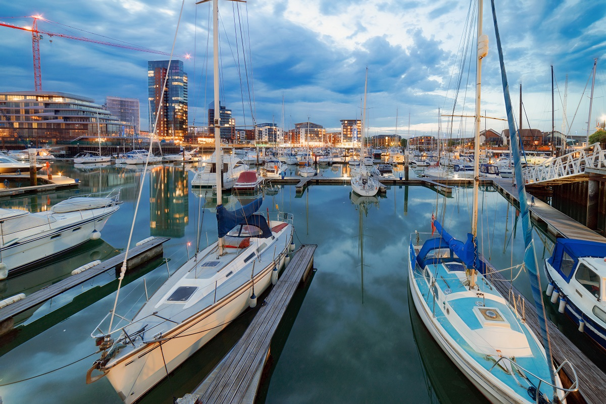 An image of various boats in the water in Southampton docks with the city in the background at dusk
