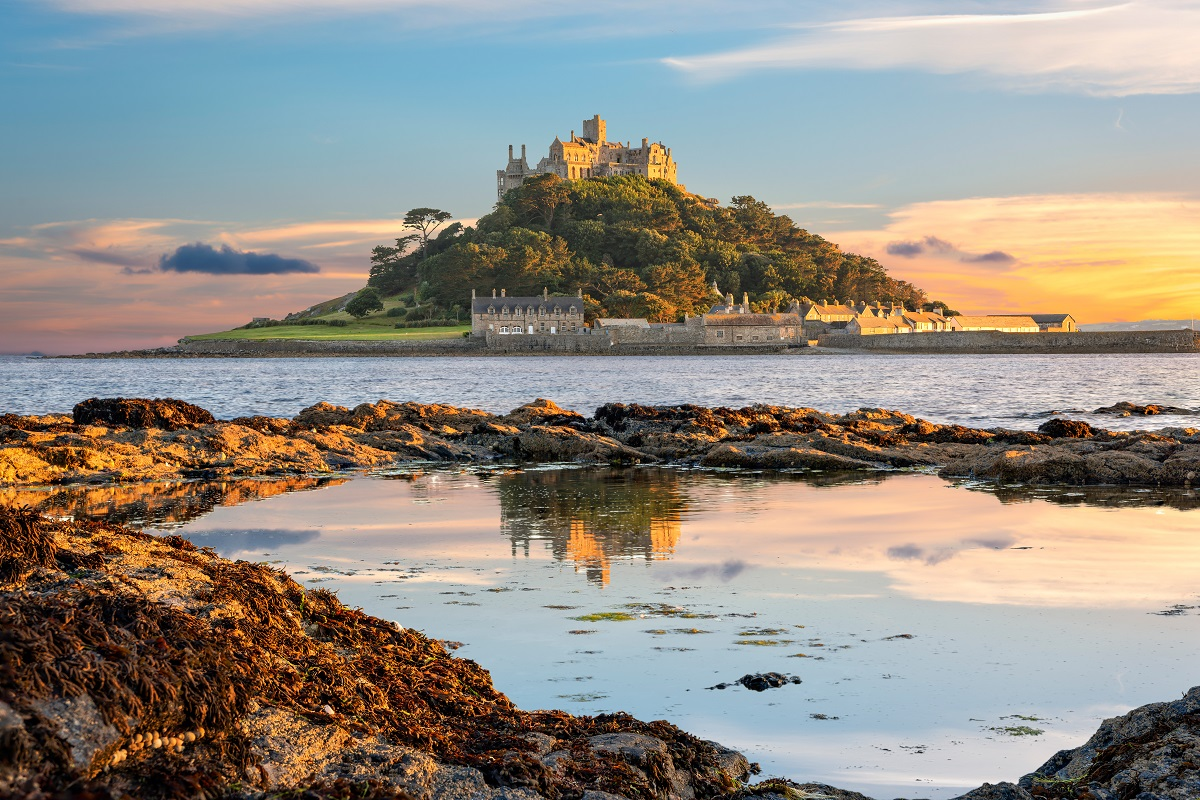 An image of the island that St Michael's Mount sits on taken from the beach at sunset