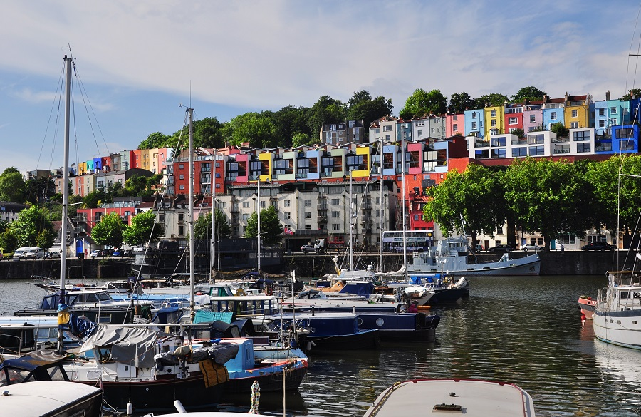 Boats docked in a body of water with colourful houses on the shore in Bristol.