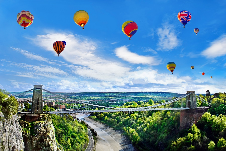 A large suspension bridge is surrounded by blue skies filled with hot air balloons in Bristol. Riding in a hot air balloon is one of the best things to do in Bristol.