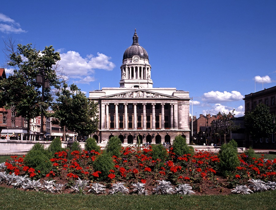 Nottingham Council House, a large white building, with red flowers in the foreground.