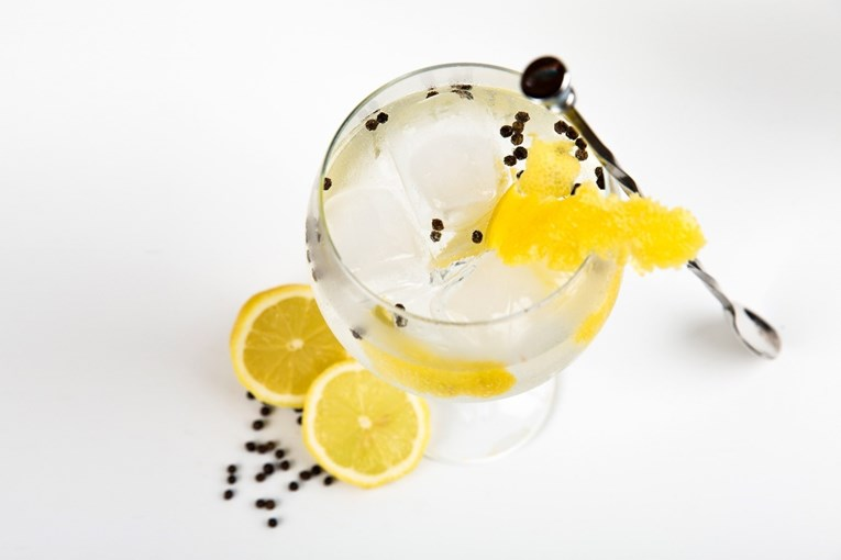A shot looking down onto a gin goblet with a lemon cut in half sat next to the glass, a stirrer, large ice cubes and juniper berries in the drink