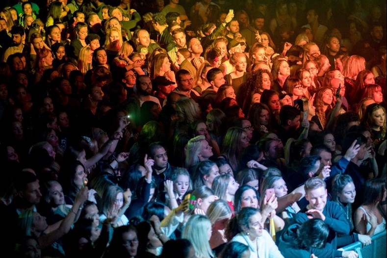A large crowd of music fans watching a concert with red and yellow lights shining down on them