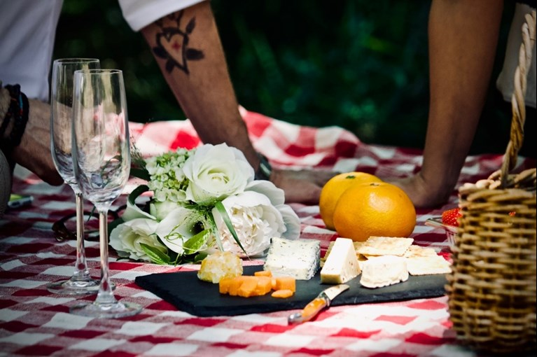 A couple enjoy a cheeseboard on a picnic blanket, complete with oranges strawberries and two champagne glasses at one of the best picnic spots in the UK