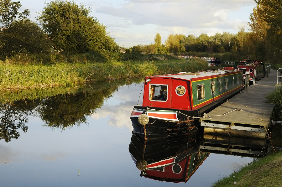 A canal boat sits on a peaceful stretch of water surrounded by trees in Edinburgh.