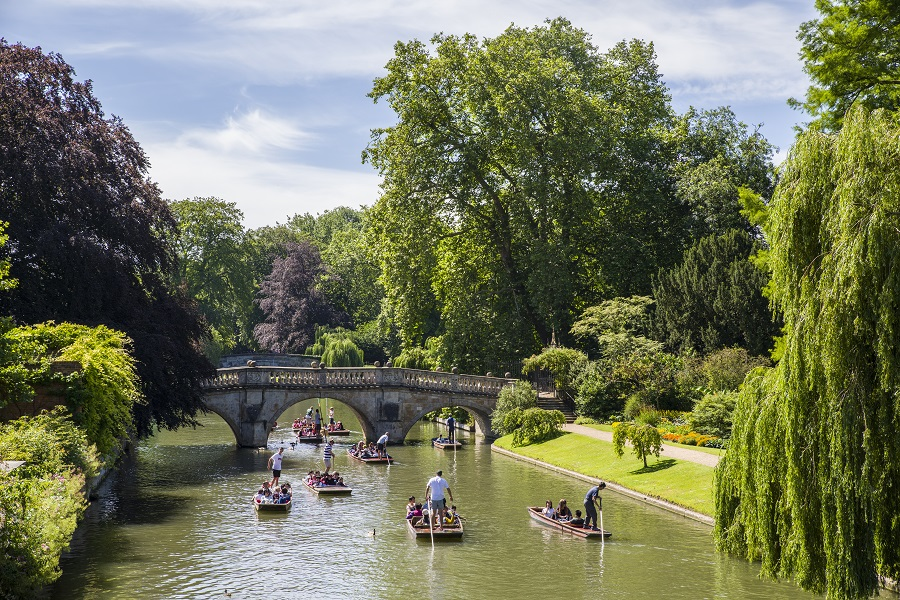 People travel down a river on punts surrounded by trees, one of the most popular boat rental options in the UK