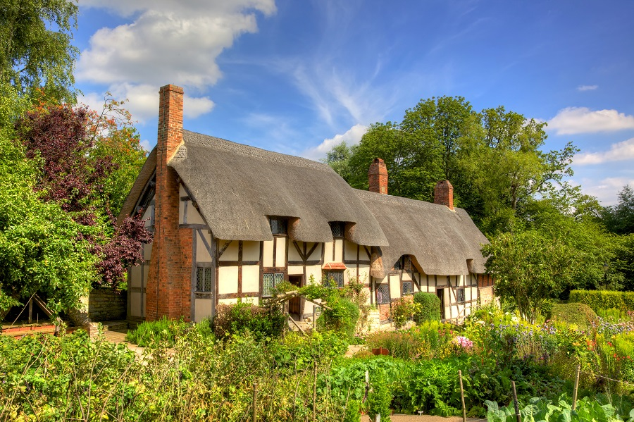 Shakespeare's wife Anne Hathaway's thatched roof cottage surrounded by green plants in Stratford.