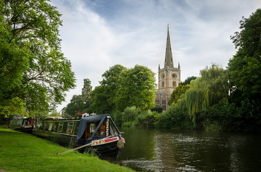 A canal boat on the River Avon with the Holy Trinity Church in the background in Stratford.
