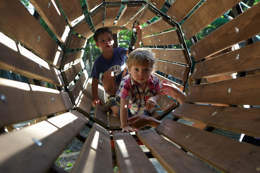 Two little boys climb through a wooden tunnel at Goldhill Adventure Playground in Leicester.