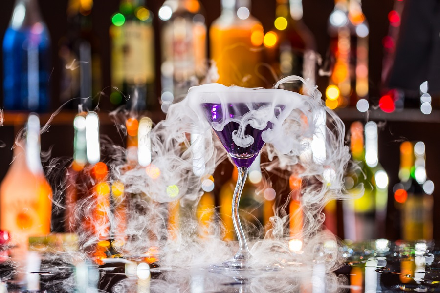 Smoke coming out of cocktail glass filled with purple liquid in a secret bar in Edinburgh