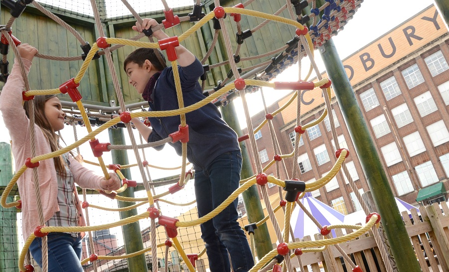 A boy and girl climb a rope net in the Adventure Play Area at Cadbury World, Birmingham.