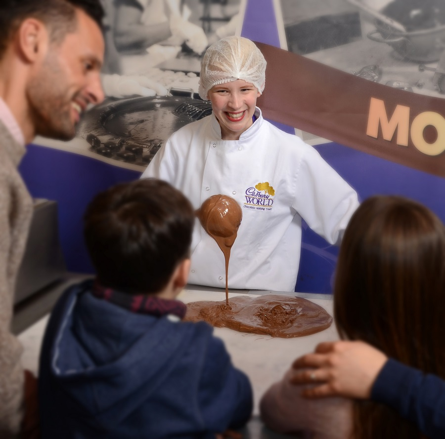 A woman wearing a white coat and a net on her head teaching families how to make chocolate at Cadbury World, Birmingham.