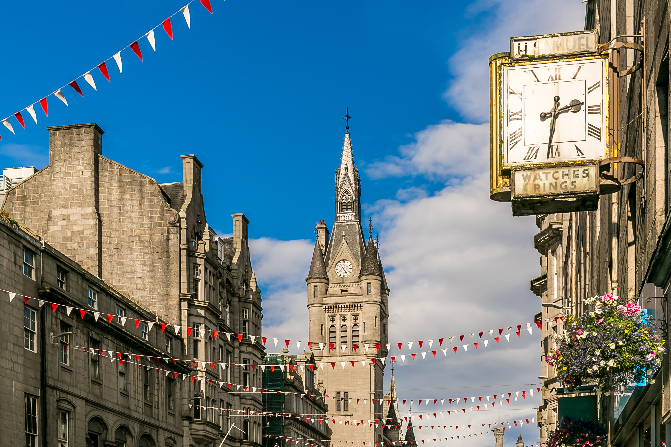 A tall pointed building on the left and a clock on the right in a sunny Aberdeen.