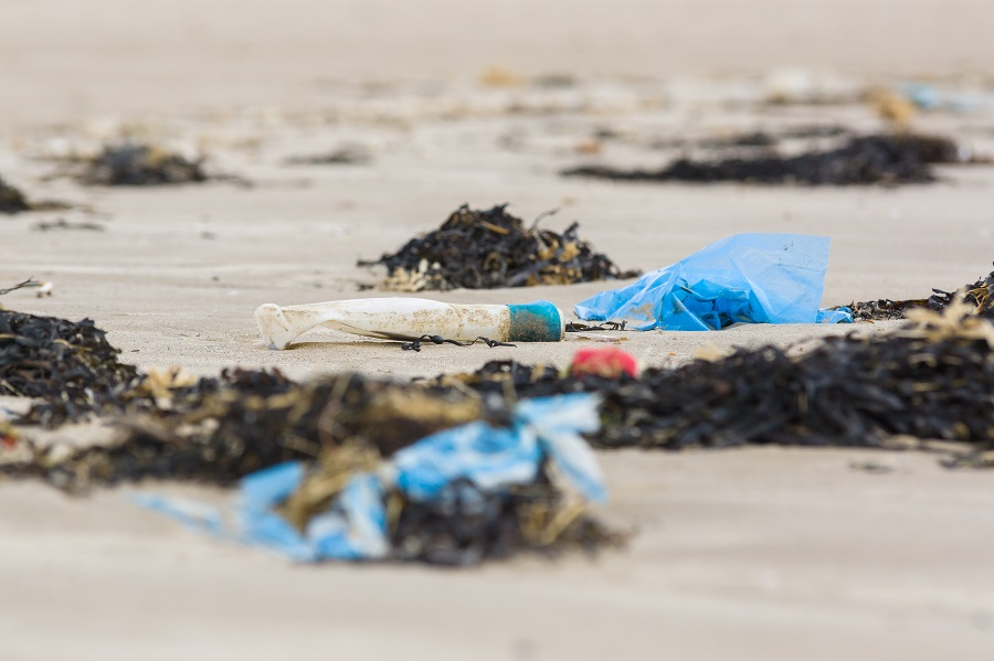 A plastic bottle and plastic bag lay discarded on sand during a Great British Beach Clean