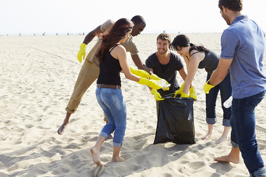 A group of people put litter in a big bin bag during the Great British Beach Clean