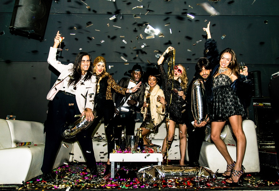 A group of 7 people dancing in front of a white sofa throwing glitter in the air