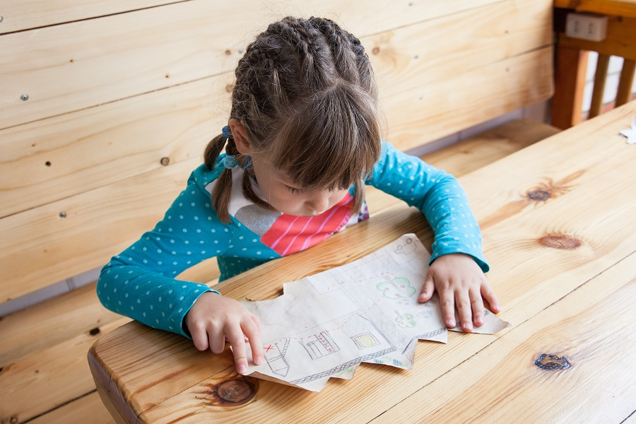 Little girl reading a treasure map on a wooden table in Weston-super-Mare.
