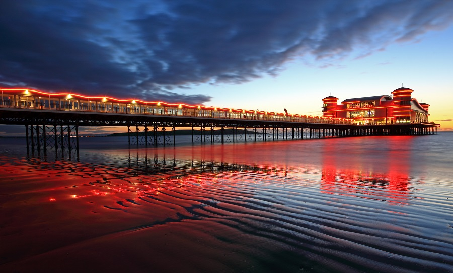 A view of the pier at sunset from the beach with red, orange and yellow lights illuminating the pier