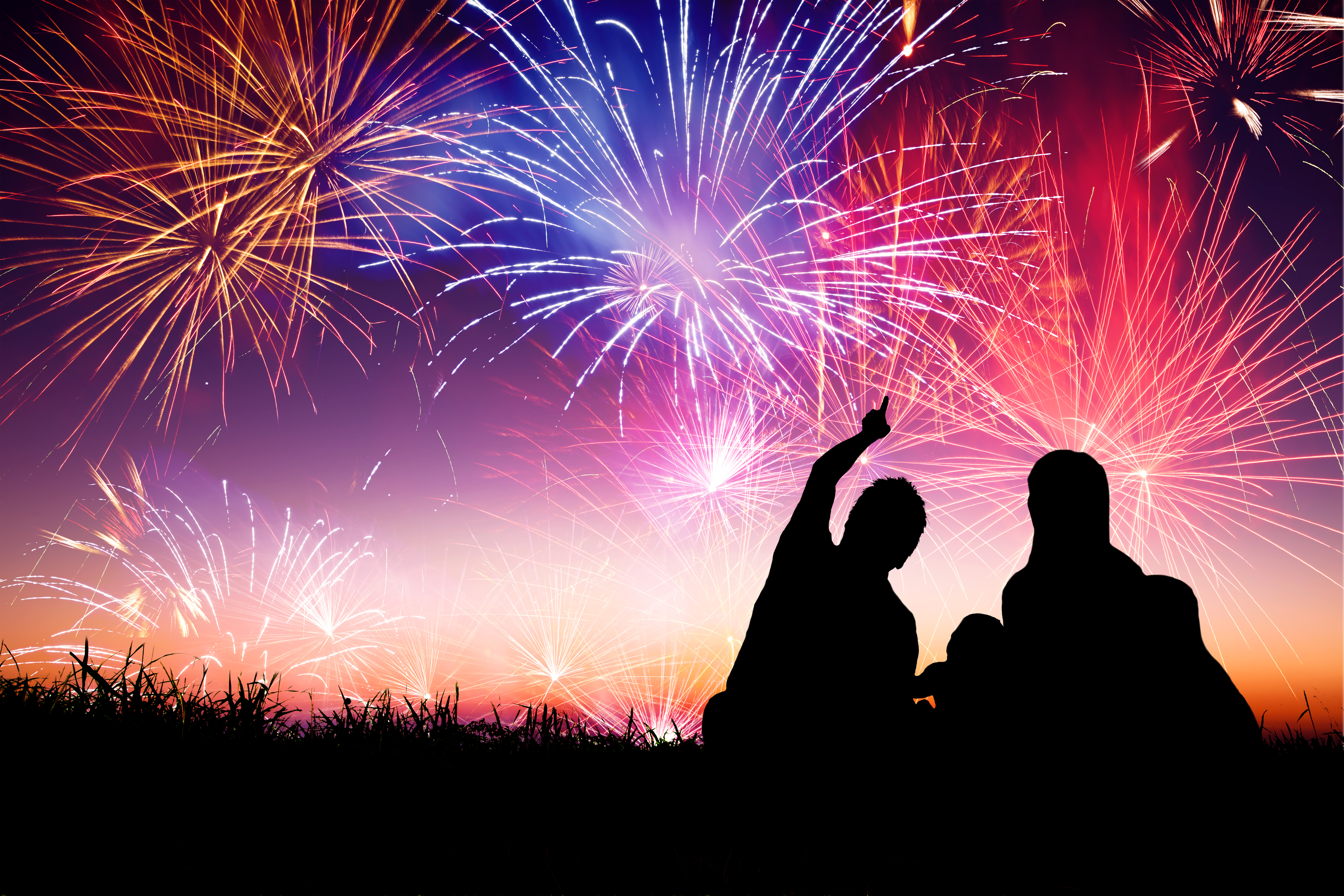 The silhouette of a couple watching brightly coloured fireworks at night at the best bonfire nights in the UK