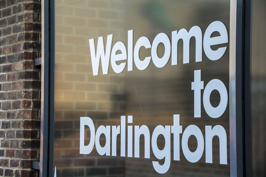 A window with white letters spelling 'Welcome to Darlington'