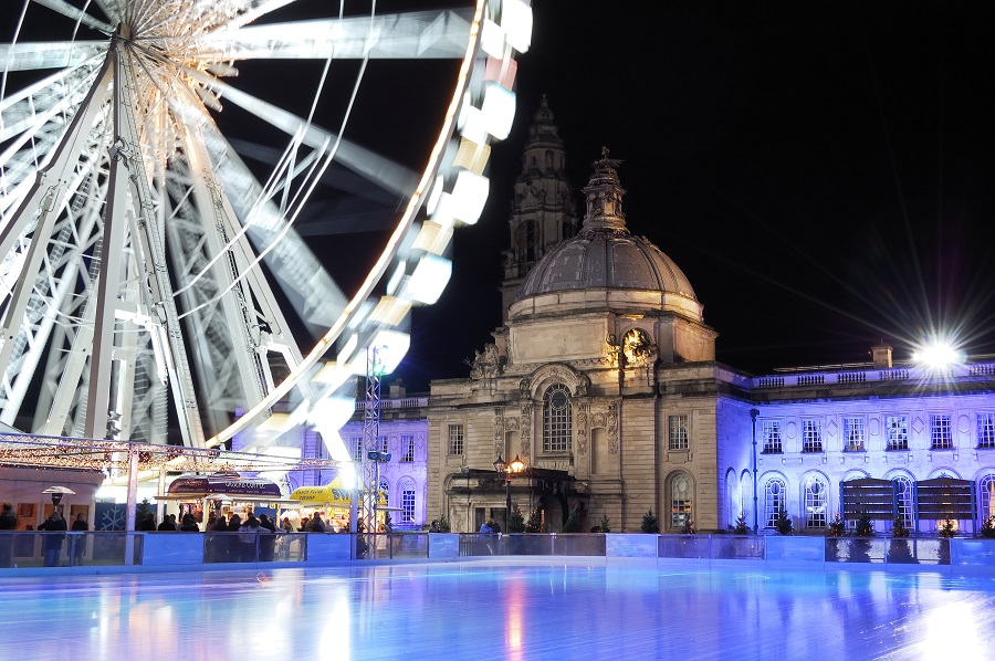 A Christmas ice rink in Cardiff with a dome shaped building and a lit up ferris wheel as a backdrop.