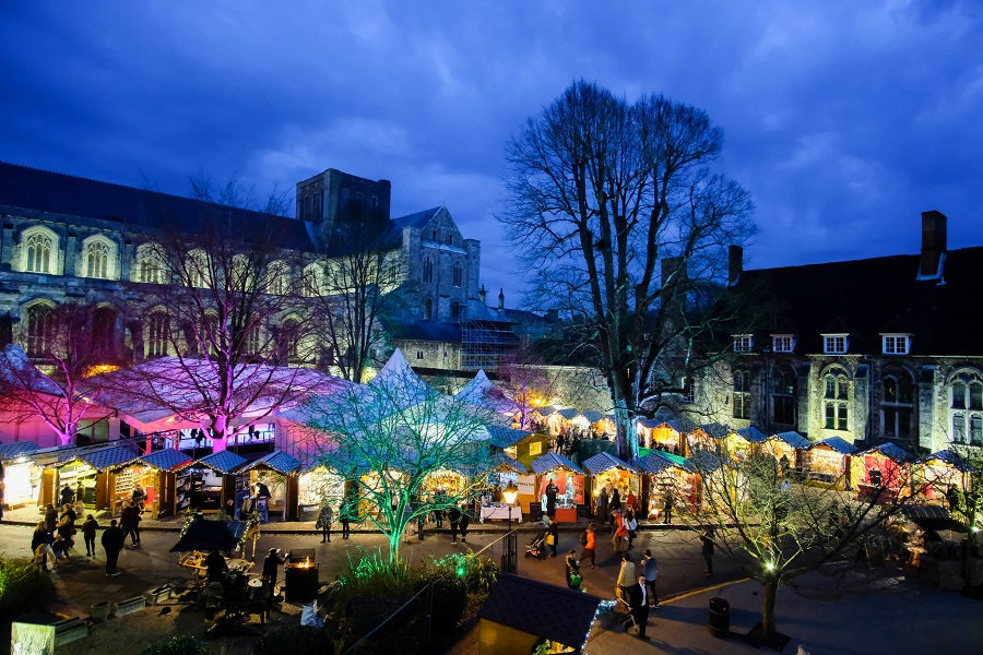 Multi-coloured lights dotted around small houses with people walking by at Winchester Cathedral outdoor ice rink.