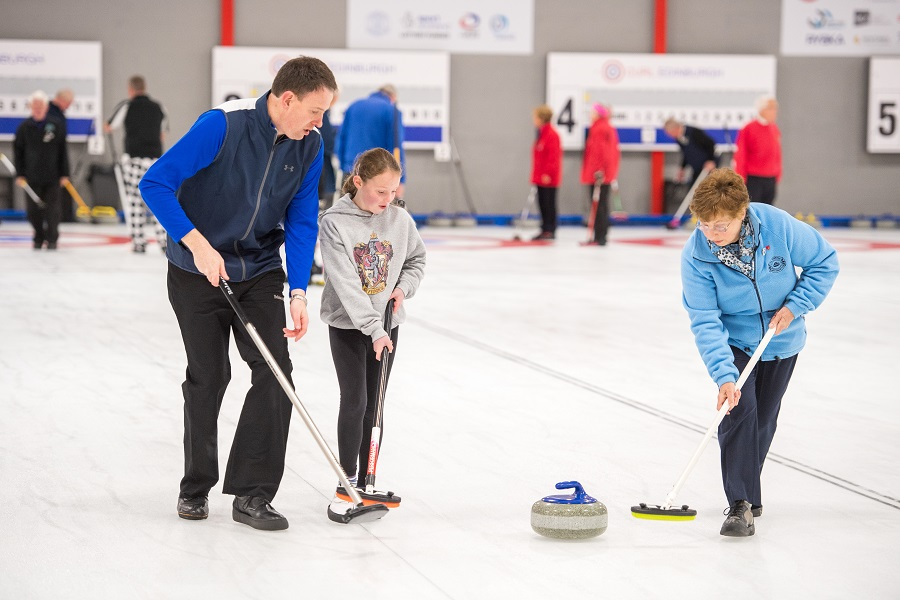 A man, a girl and an older lady holding brooms following a stone on an ice rink. Curling is one of the best winter sports in the UK.