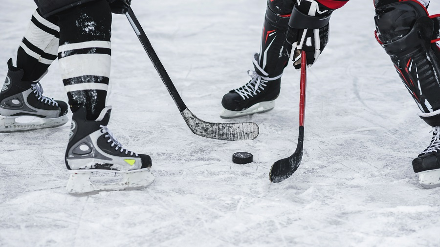 Two people wearing ice skates and holding hockey sticks on ice around a small disc ice puck shows ice hockey as a great UK winter sport.