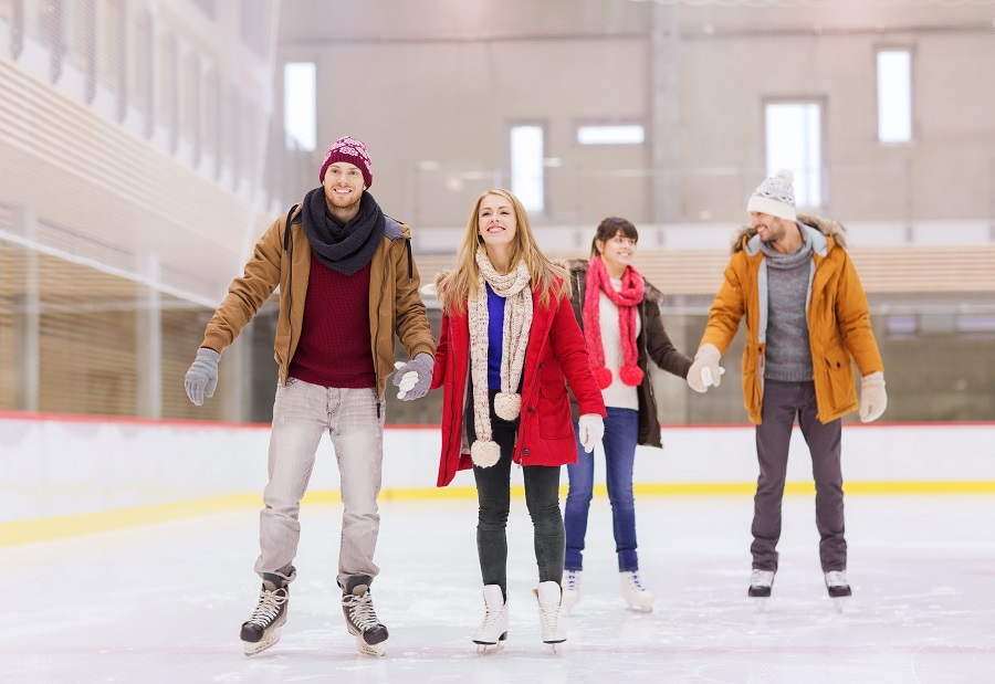 Two couples holding hands as they ice skate on an indoor ice rink.