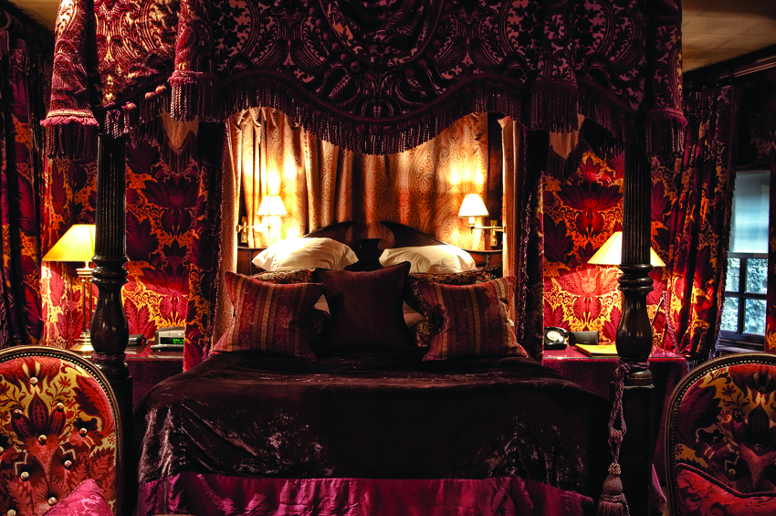 A dimly lit room with a four poster bed draped in silk at The Witchery in Edinburgh, one of the most romantic hotels in the UK.