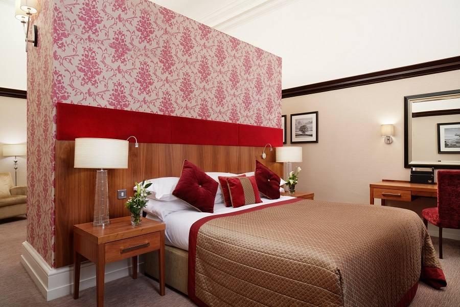 A big bed in the middle of a red and gold themed room in The Grand Hotel & Spa, one of the most romantic hotels in the UK.