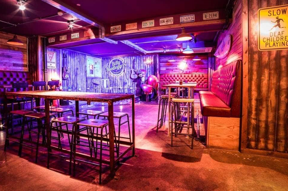 A pink lit underground bar with tall tables and stools in one of Newcastle's Secret Bars.