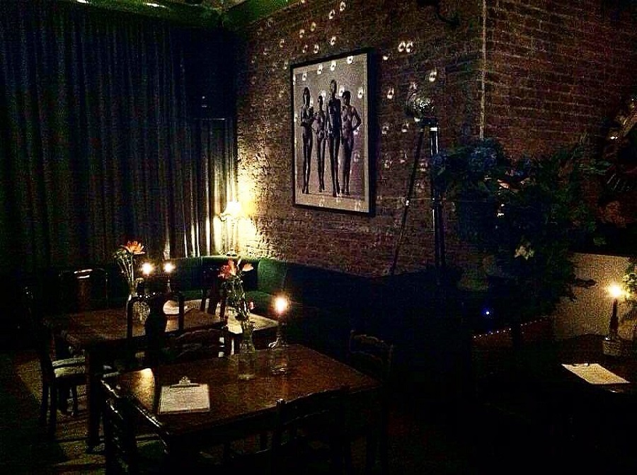 A dark room with candle lit tables and a picture hung up on a brick wall in one of Newcastle's secret bars.