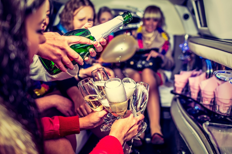 A green bottle of liquid being poured into champagne flutes in the back of a limo to celebrate a hen do in the UK.