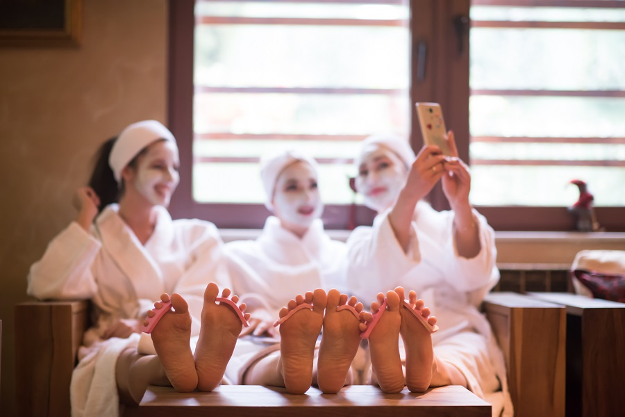 Three girls in white dressing gowns and headbands take a selfie with face masks on and toe separators between their toes on a UK hen do.