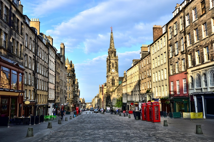 The UK ultra-marathon in Edinburgh starts on the Royal Mile, a partly cobbled street with old, weathered buildings either side and a church in the background.