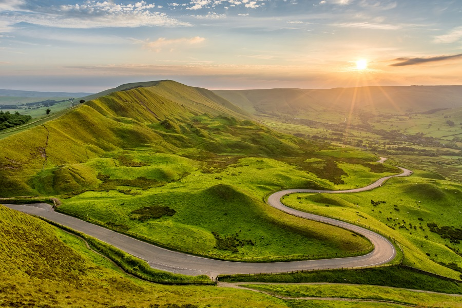 A tarmac road winds through rolling green hills in the Peak District, the route for the UK's most challenging ultra-marathon.