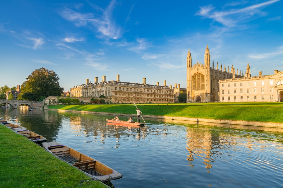 A man paddles a punt down the River Cam on a sunny day in Cambridge, passing a grand university building – a perfect activity for world poetry day.
