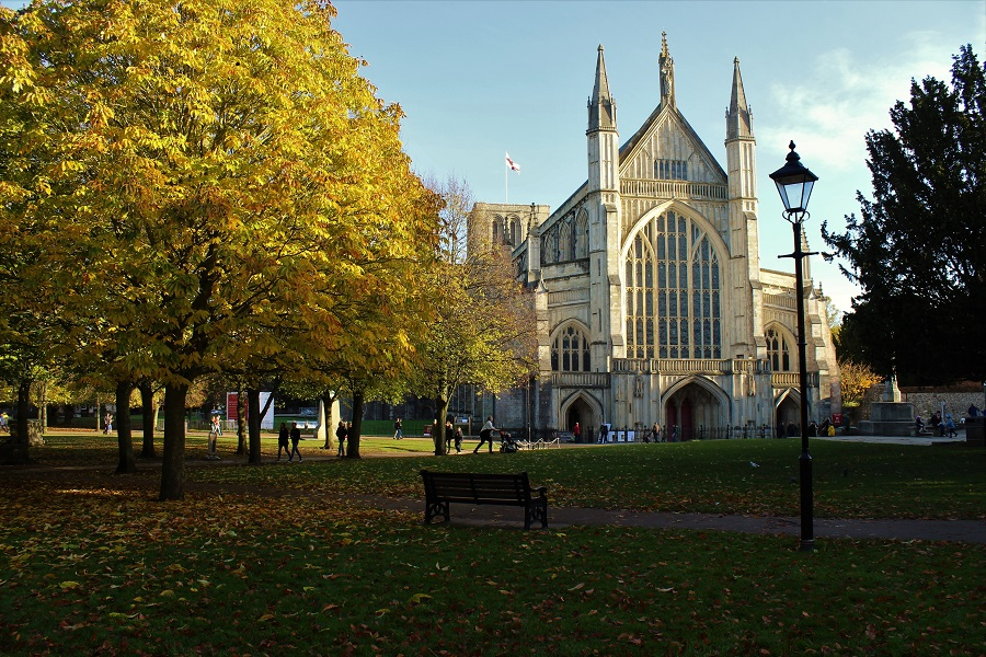 Winchester Cathedral stands tall in the sunshine surrounded by Autumnal trees, a lovely image for World Poetry Day.