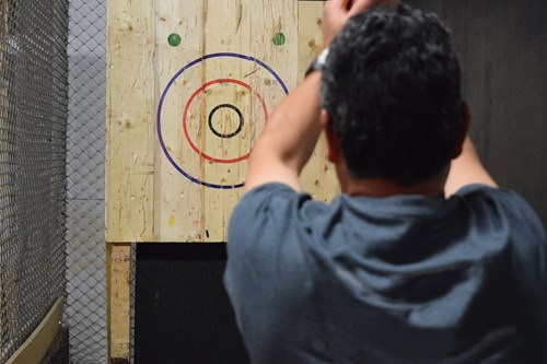 Man throwing axe at wooden board, axe throwing is a great date idea in Birmingham.