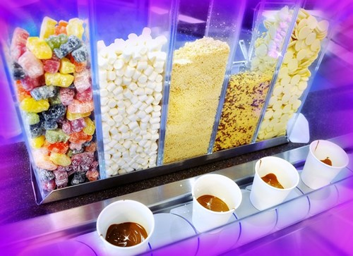 Melted chocolate in small cups and sweeties at Cadbury World, Birmingham, a day out that's a great date idea in Birmingham