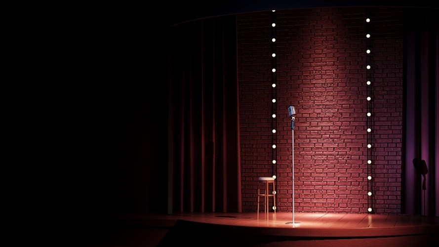 A comedy stage with a microphone and stall.
