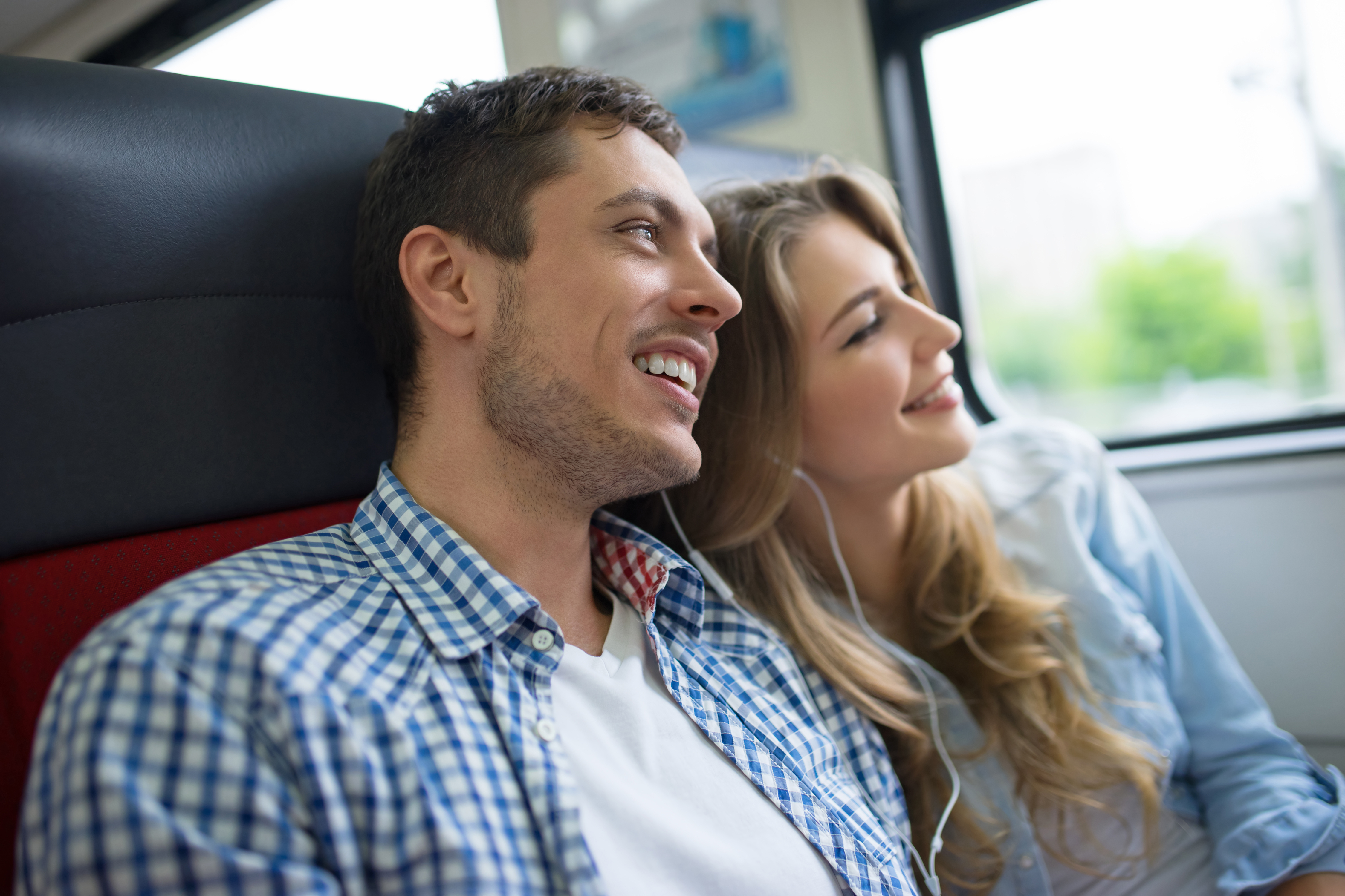 Young couple on a train smiling