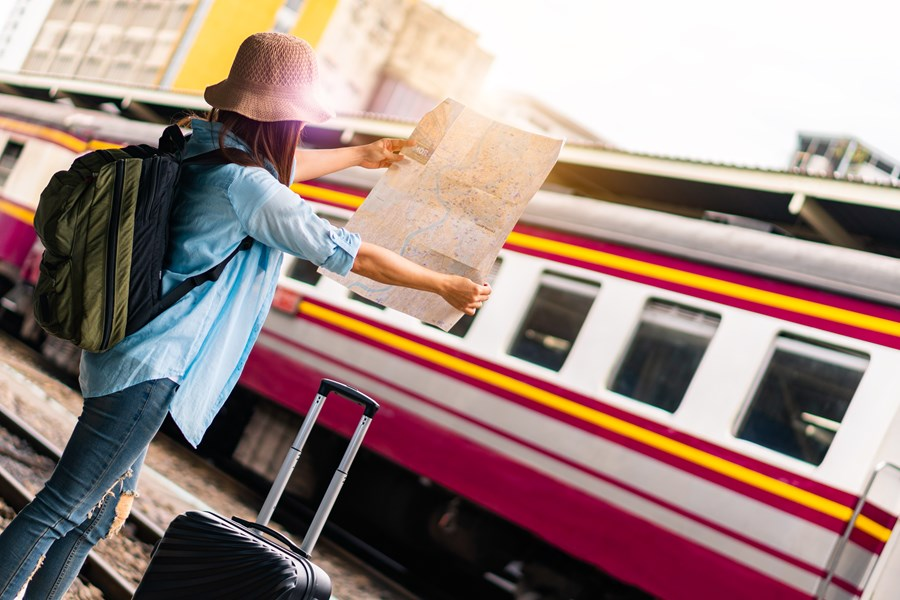 Young female wearing a backpack and sun hat stands on train platform holding a large map.