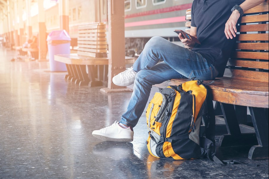 Man wearing jeans and white trainers sits waiting for a train with a large backpack by his feet.