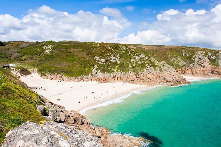 A landscape photograph of Porthcurno Beach in Penzance in the summer.