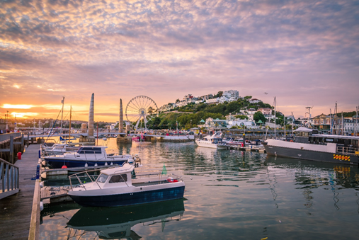Spending time at the beautiful Torquay marina, pictured here at sunset with boats in the foreground and attractions and the town behind, is a popular thing to do in Devon.