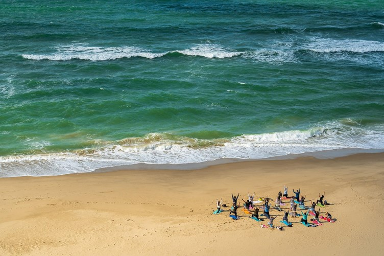 Yoga class taking place next to the ocean on Bournemouth Beach.